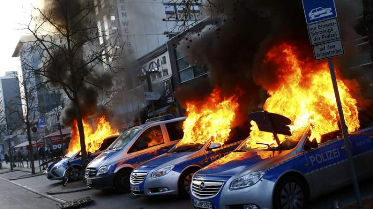 Four German police cars set on fire by anti-capitalist protesters burn near the new ECB headquarters in downtown Frankfurt